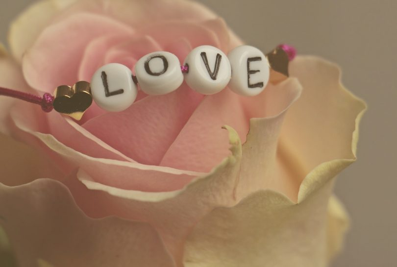 Rosa amb un braçalet amb la paraula LOVE