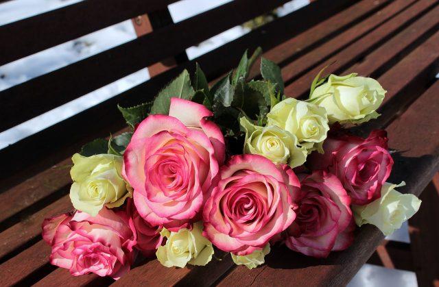 Ram de roses grogues i vermelles sobre un banc