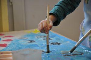 Nen a l'escola pintant un mural