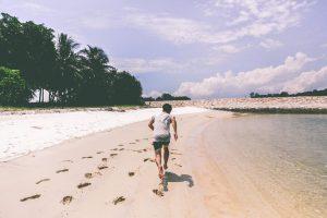 Un home corre a la platja