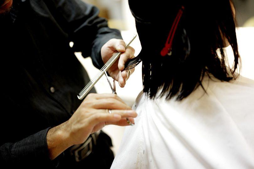 Perruquer tallant el cabell a una dona