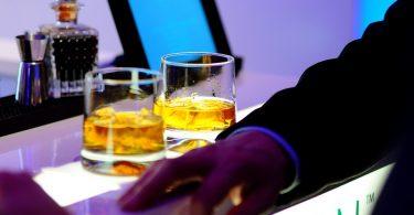 Home a una barra d'un bar amb dos gots de whiskey