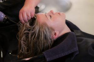 Perruquer netejant el cap a una clienta