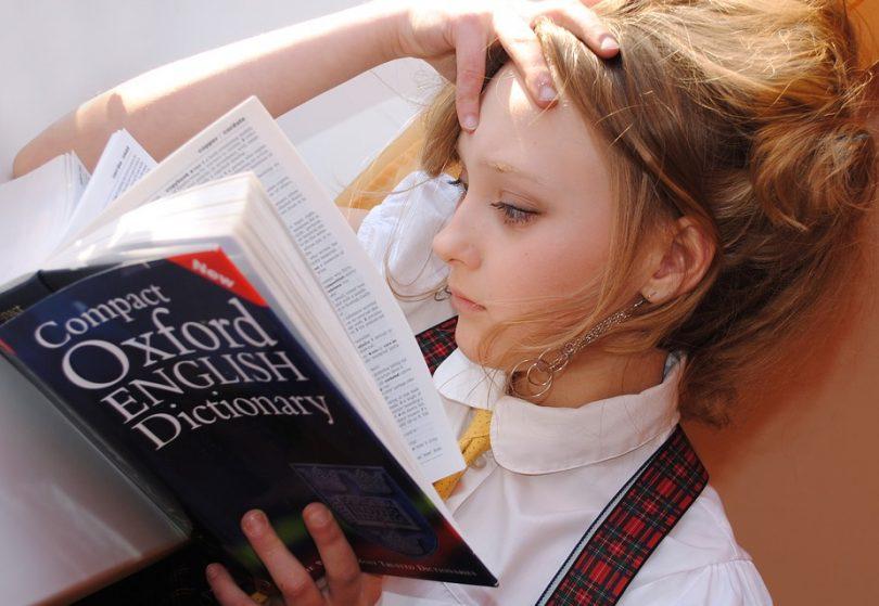 Noia llegint un diccionari anglès