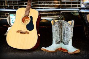 Guitarra i botes de country davant d'un cotxe americà