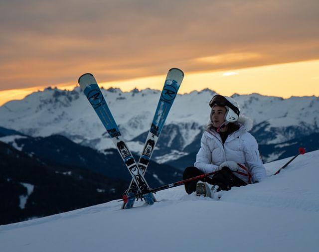Una noia descansant de l'esquí a la neu