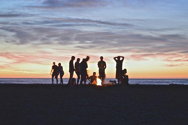 Grup d'amics davant d'una foguera a la platja