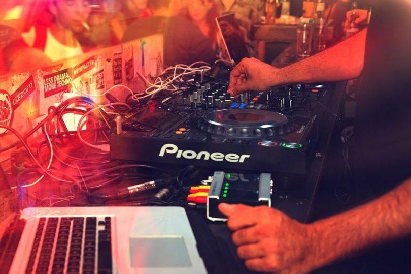 DJ treballant en la seva taula de mescles a un club nucturn