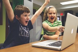 Nens es diverteixen jugant a l'ordinador