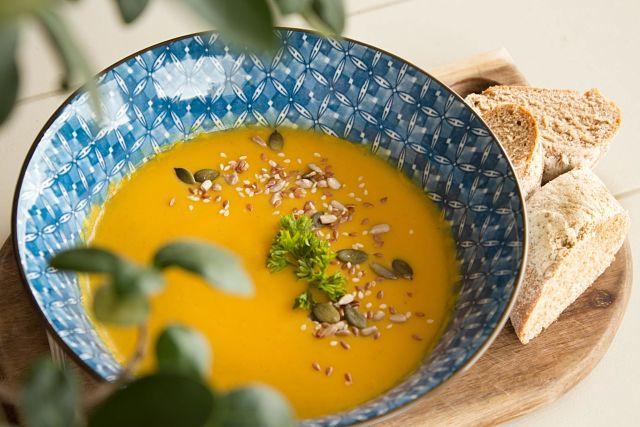 Sopa de carbassó amb pà a una taula d'un restaurant