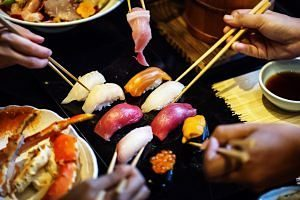 Amics gaudint a un restaurant de sushi