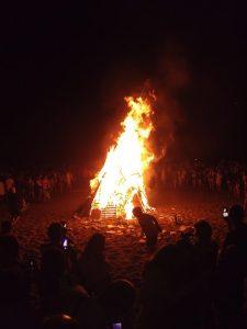 Gent envoltant una espectacular foguera de Sant Joan