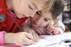 Dos nens dibuixen a una llibreta a classe