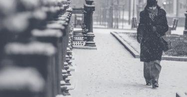 Noia camina per una ciutat nevada