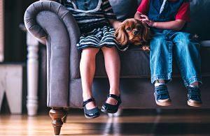 Nens als sofà gaudint de la companyía d'un gos
