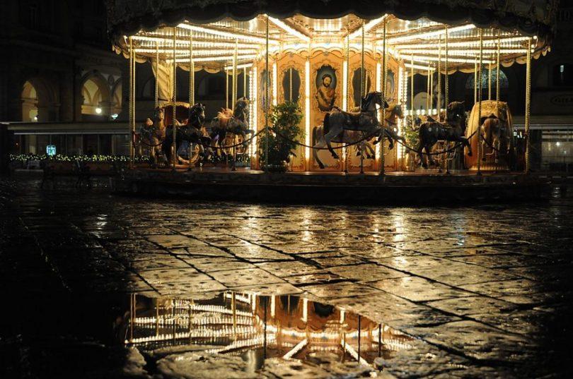Carrusel tradicional amb llums sobre el sòl humit