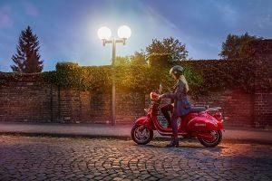 Noia amb una scooter al carrer