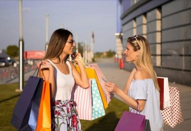 Noies parlant amb bosses de compres