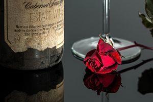 Ampolla de vi luxosa i una rosa