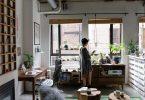 Dona davant la finestra al menjador de casa
