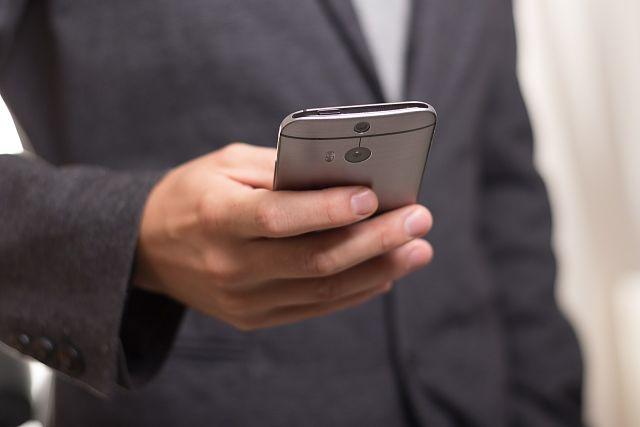 Empresari consultant el seu telèfon mòbil