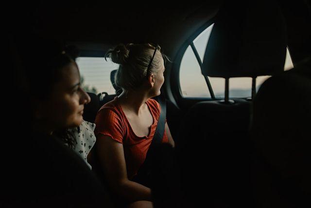 Noies a la part de darrera d'un cotxe gaudint de les vistes