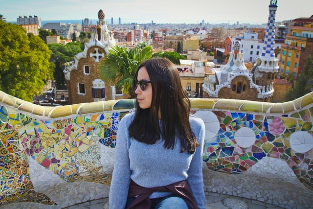 noia asseguda a un banc del Park Güell de Barcelona