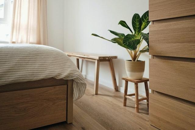 dormitori amb un llit, calaixera i planta de decoració